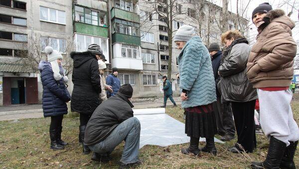 Жителям домов города Ясиноватая, пострадавшим в результате обстрела, выдают пленку, чтобы закрыть разбитые окна. 21 декабря 2017