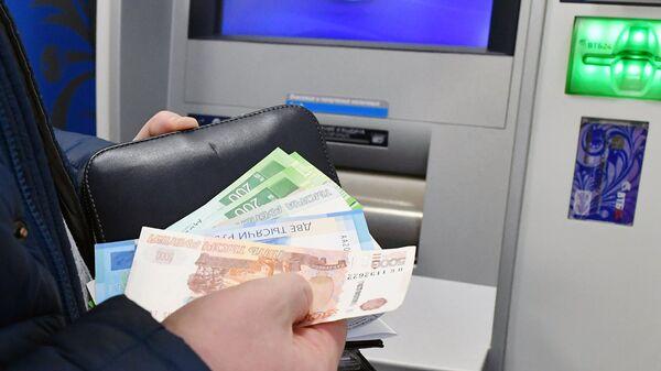 Снятие денег в банковском терминале. Архивное фото