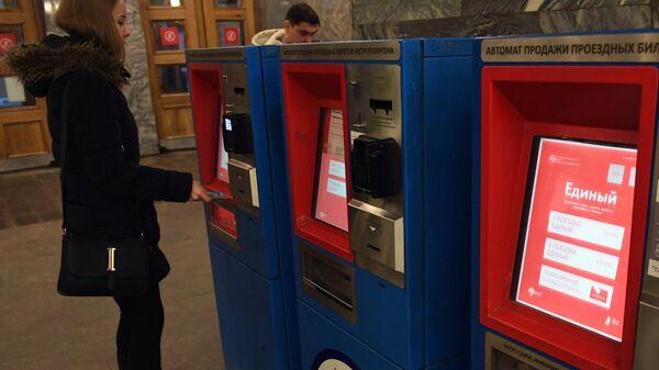 Девушка пополняет карту Тройка в автомате продажи проездных билетов московского метро