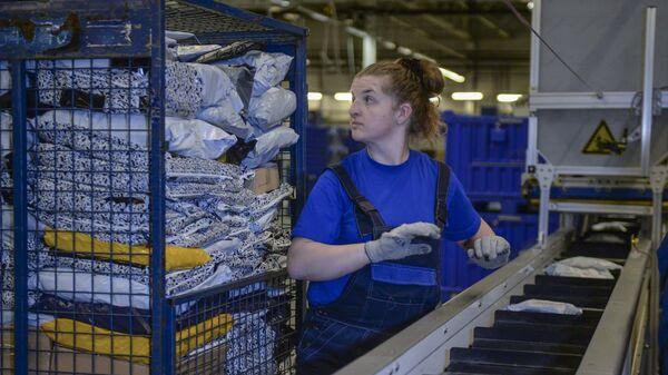 Работница на новой линии для сортировки почтовых отправлений в автоматизированном сортировочном центре Почты России в Санкт-Петербурге
