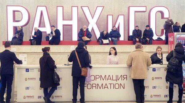 Посетители у стойки информации на VIII Гайдаровском форуме Россия и мир: выбор приоритетов в Москве