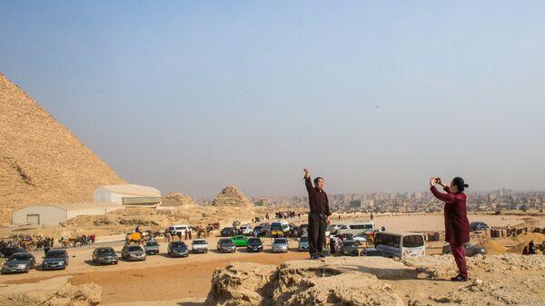 Туристы фотографируются на фоне древнеегипетских пирамид в Эль-Гизе, пригороде Каира