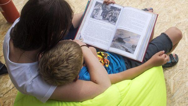Женщина и ребенок читают книгу на одной из площадок Московского фестиваля Книги России на Красной площади