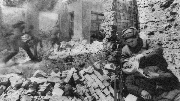 Сталинград. Декабрь 1942 г. Уличный бой. Санитарка перевязывает раненого