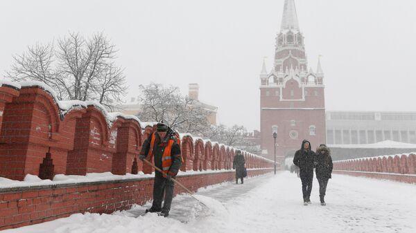 Сотрудник коммунальной службы чистит снег на мосту между Кутафьей и Троицкой башнями Московского Кремля во время снегопада