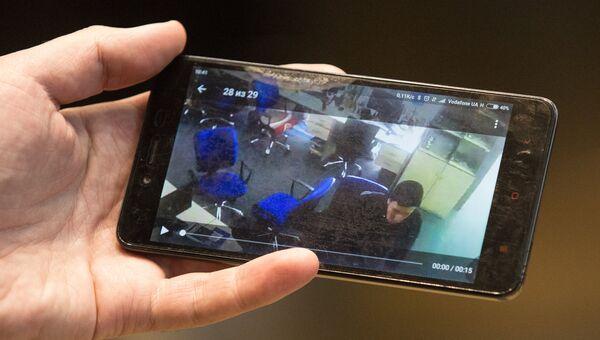 Человек смотрит на смартфоне трансляцию с камер наблюдения редакции газеты Вести, где проходят обыски. 8 февраля 2018