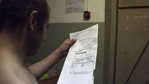 Мужчина держит квитанцию оплаты коммунальных услуг