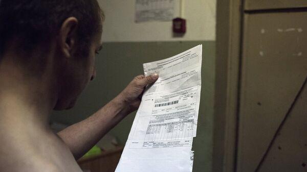 Мужчина держит квитанцию оплаты коммунальных услуг. Архивное фото
