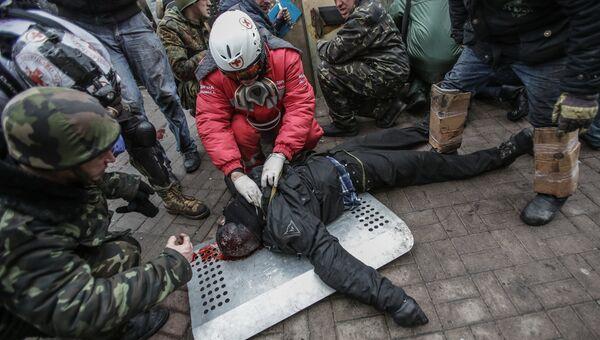Сторонники оппозиции оказывают помощь раненому во время столкновений на площади Независимости в Киеве
