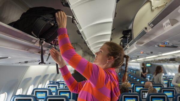 Девушка убирает ручную кладь в отсек в салоне самолета