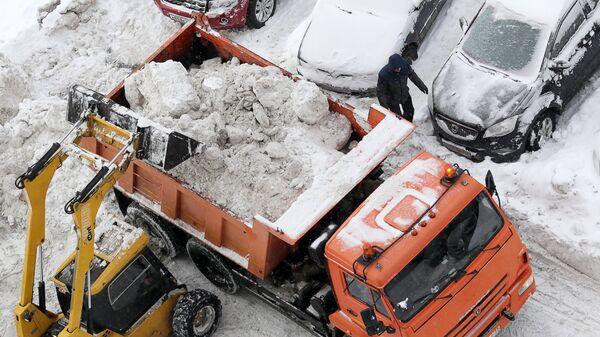 Погрузка снега в кузов грузового автомобиля на придомовой территории в Москве