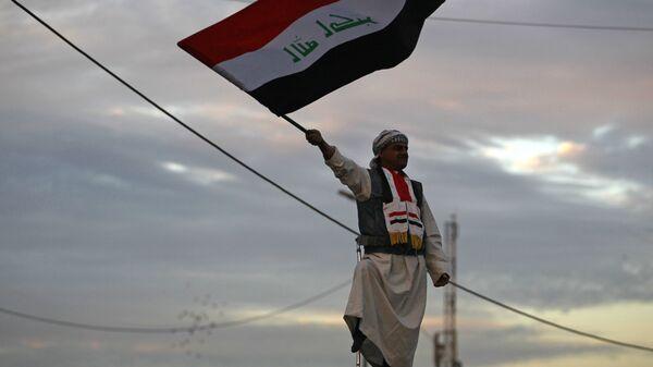 Мужчина с флагом Ирака в Багдаде. Архивное фото