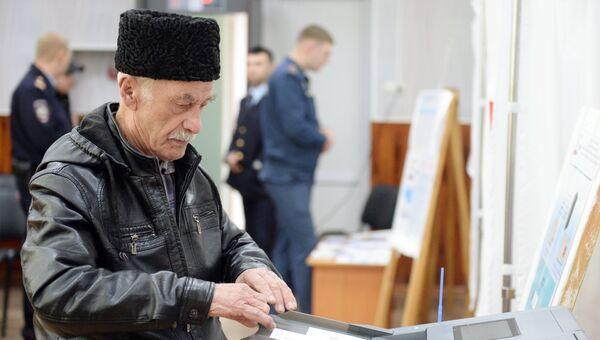 Мужчина опускает бюллетень в урну во время голосования на выборах президента Российской Федерации на избирательном участке в Симферополе.18 марта 2018