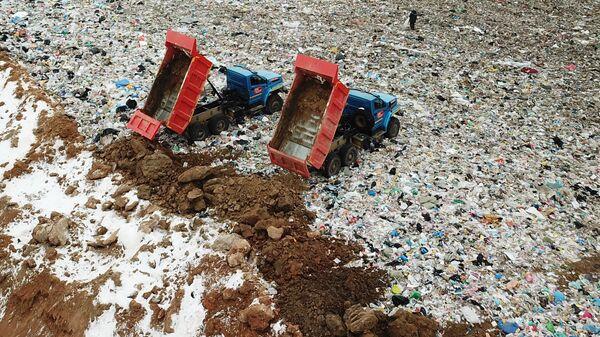 Сотрудники полигона твердых бытовых отходов Ядрово в Московской области засыпают грунтом площадку полигона для нейтрализации неприятных запахов