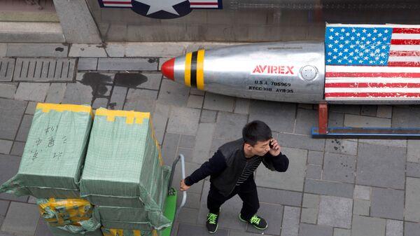 Мужчина с тележкой, груженой коробками с товаром, в Пекине