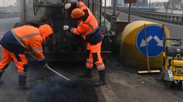 Рабочие ремонтируют участок дороги в Москве