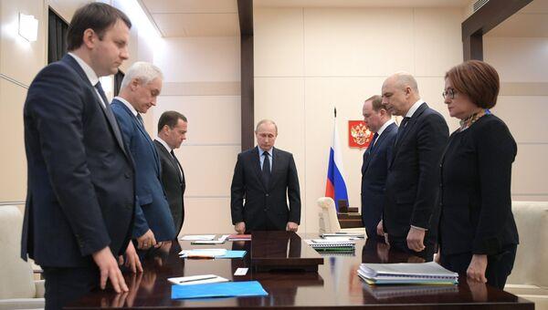 Президент РФ Владимир Путин и участники совещания по экономическим вопросам во время минуты молчания в знак траура по погибшим при пожаре в Кемерове. 28 марта 2018