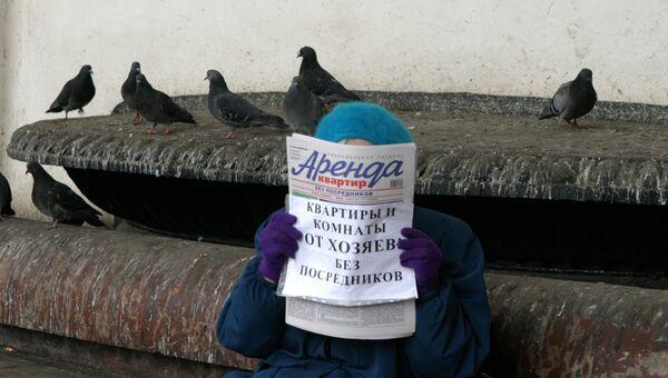 Женщина держит в руках газету Аренда квартир