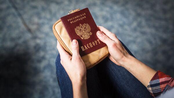 Девушка держит российский паспорт