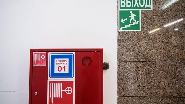 Пожарный шкаф и указатель направления эвакуации
