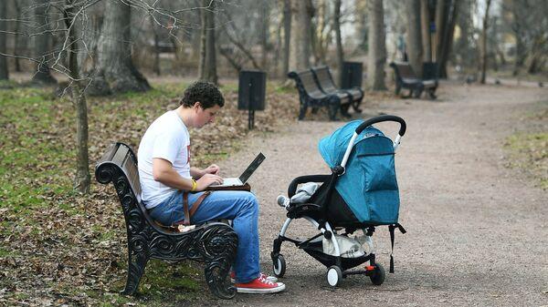Молодой человек с коляской в Нескучном саду в Москве