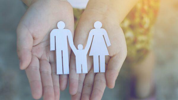 Ребенок с фигуркой семьи в руках. Архивное фото