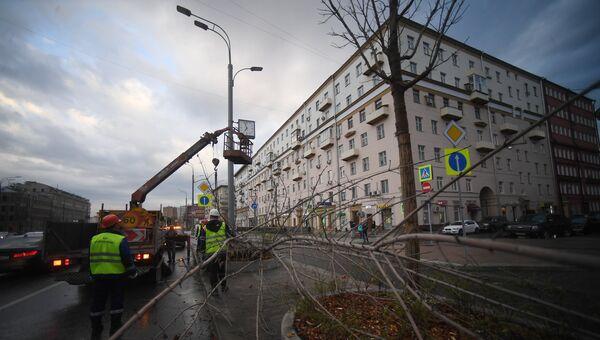Рабочие грузят рекламный щит, поваленный ураганным ветром на углу Смоленского бульвара и 1-ого Неопалимовского переулка в Москве. 21 апреля 2018
