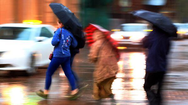 Пешеходы на улице в Москве во время сильного дождя. Архивное фото