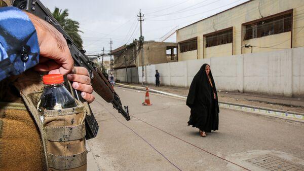 Сотрудник федеральной полиции Ирака возле избирательного участка в районе Каррада в Багдаде. 12 мая 2018