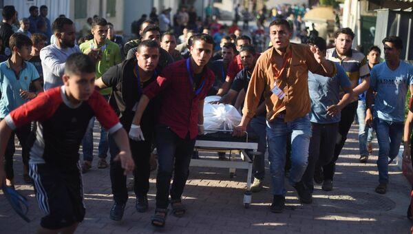 Палестинцы везут пострадавшего в столкновениях с израильскими военными на границе сектора Газа и Израиля. Архивное фото