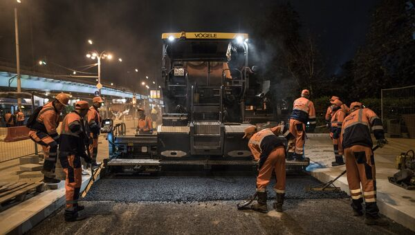Рабочие во время укладки асфальта