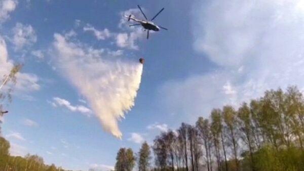 Вертолет Ми-8 во время тушения пожара на территории бывшего военного арсенала в поселке Пугачево в Удмуртии. 17 мая 2018