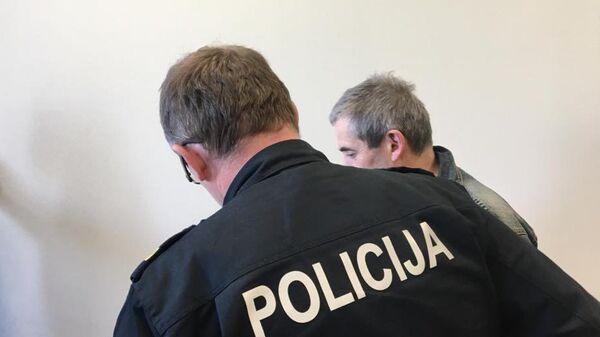 Сотрудник полиции ведет Владимира Линдермана в зал заседаний суда в Риге