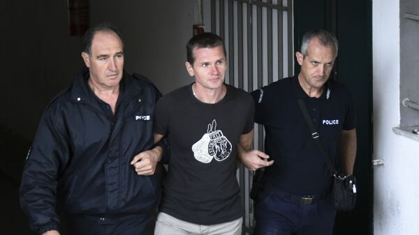 Полицейские сопровождают Александра Винника в греческом городе Салоники