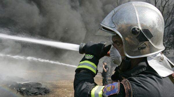 Сотрудник пожарной службы Греции во время тушения лесного пожара