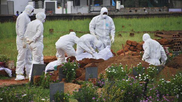 Индийские парамедики закапывают тело погибшего от вируса Нипах в городе Кожикоде