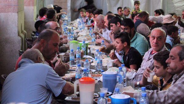 Жители Алеппо во время ужина организованного фондом имени Ахмата Кадырова и российскими офицерами ЦПВС в священный для мусульман месяц Рамадан. 28 мая 2018