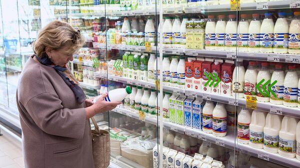 Покупатель у витрины с молочной продукцией