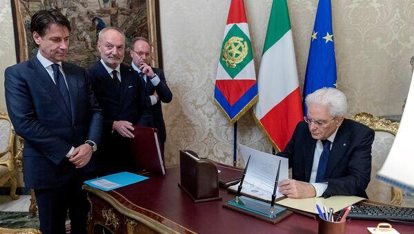 Назначенный премьер-министром Италии Джузеппе Конте смотрит, как президент Италии Серджо Маттарелла подписывает документы, Италия. 31 мая 2018