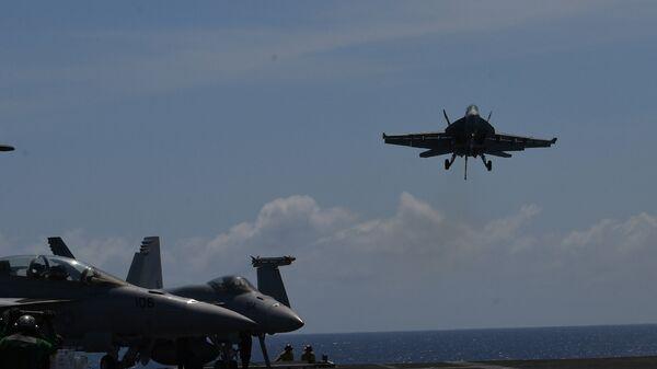 Истребитель FA-18 Hornet приземляется на авианосец Теодор Рузвельт