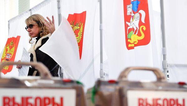 Девушка во время голосования на выборах президента РФ на избирательном участке №13-06 в Москве