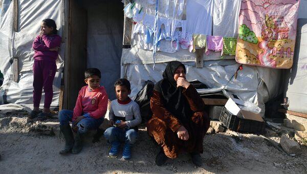 Женщина с детьми в палаточном лагере для сирийских беженцев. Архивное фото