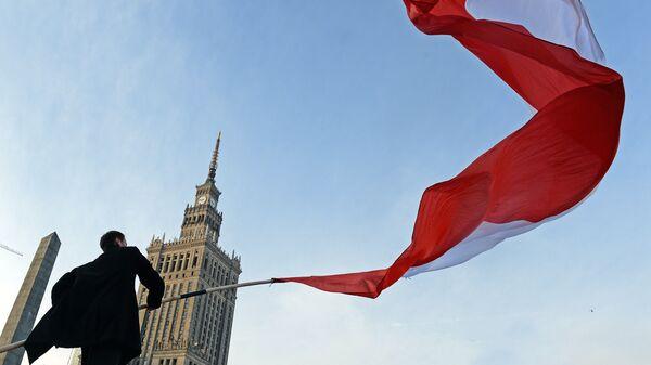 Мужчина держит польский флаг во время празднования Дня независимости в Варшаве