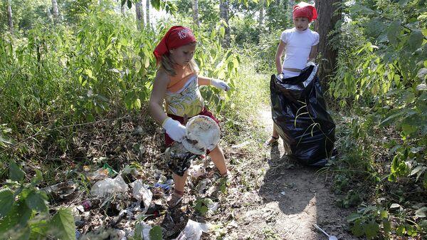 Школьники убирают мусор с прибрежной зоны