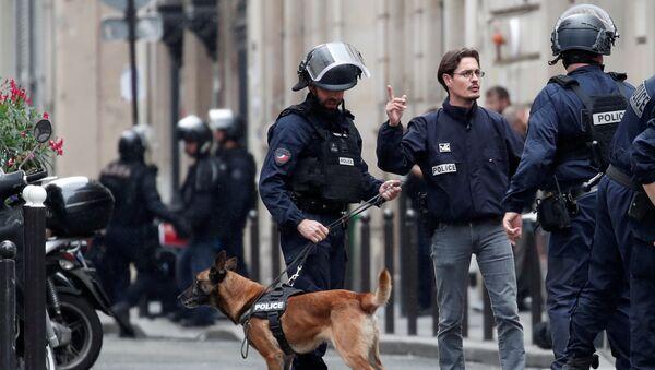 Французская полиция с собакой на улице, где человек взял людей в заложники в бизнесе-центре в Париже, Франция. 12 июня 2018