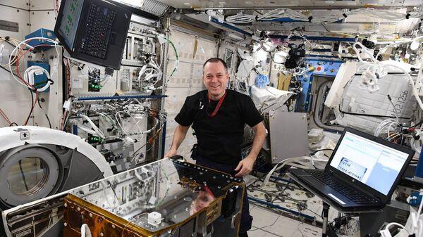 Астронавт Рики Арнольд готовится вывести зонд RemoveDebris в открытый космос