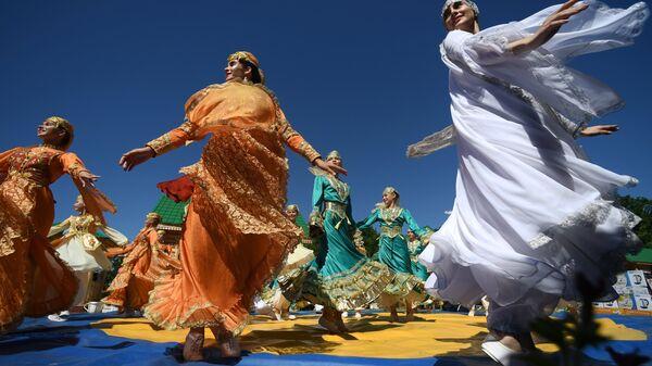 Участницы гуляний танцуют на празднике Сабантуй в Березовой роще поселка Мирный. 23 июня 2018