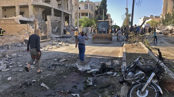 Местные жители и активисты из организации Белые каски на месте взрыва в Идлибе, Сирия. Архивное фото