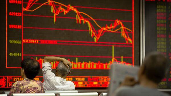 Китайские инвесторы наблюдают за котировками ценных бумаг в брокерской конторе в Пекине, КНР. Архивное фото