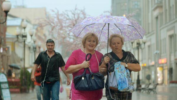 Прохожие под зонтом во время дождя в Москве